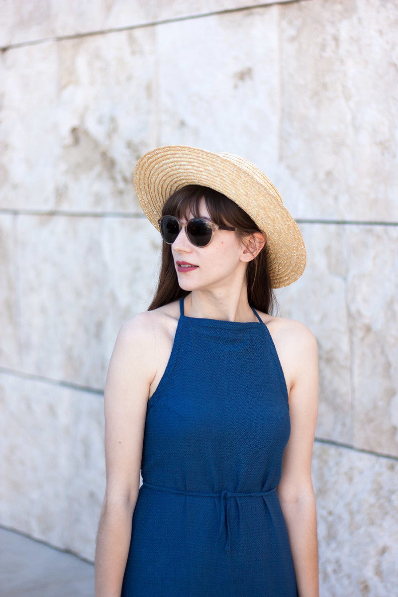 Fashion blogger wearing denim halter dress , straw hat, shwood sunglasses