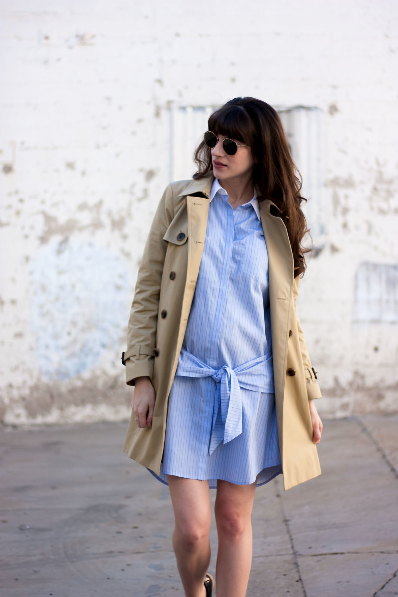 Minimalist Style Blogger wearing a tan trench coat and striped shirtdress