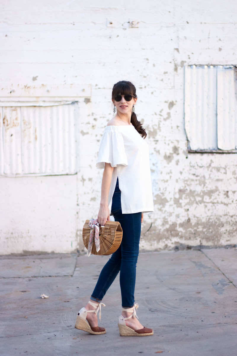 Fashion Blogger wearing white off the shoulder top with Cult Gaia Bag