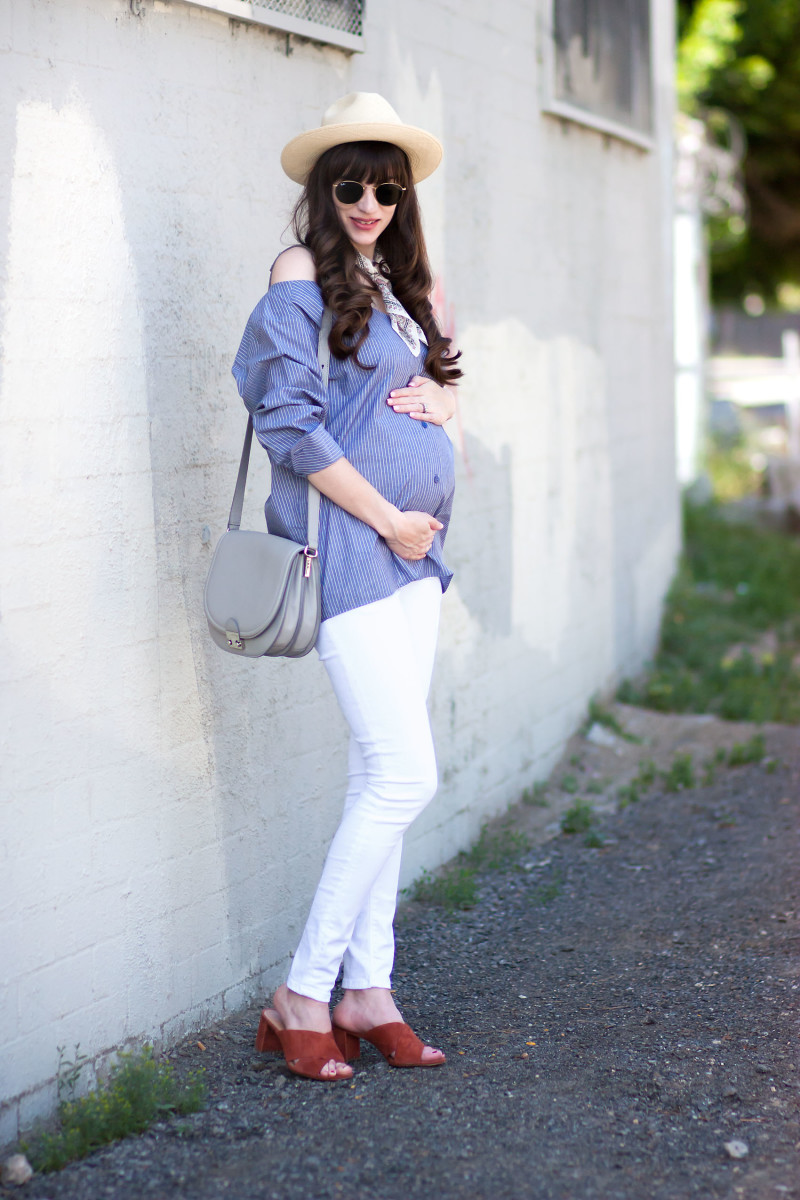 Pregnant Style Blogger wearing Minimalist off the shoulder shirt, white denim and red suede mules