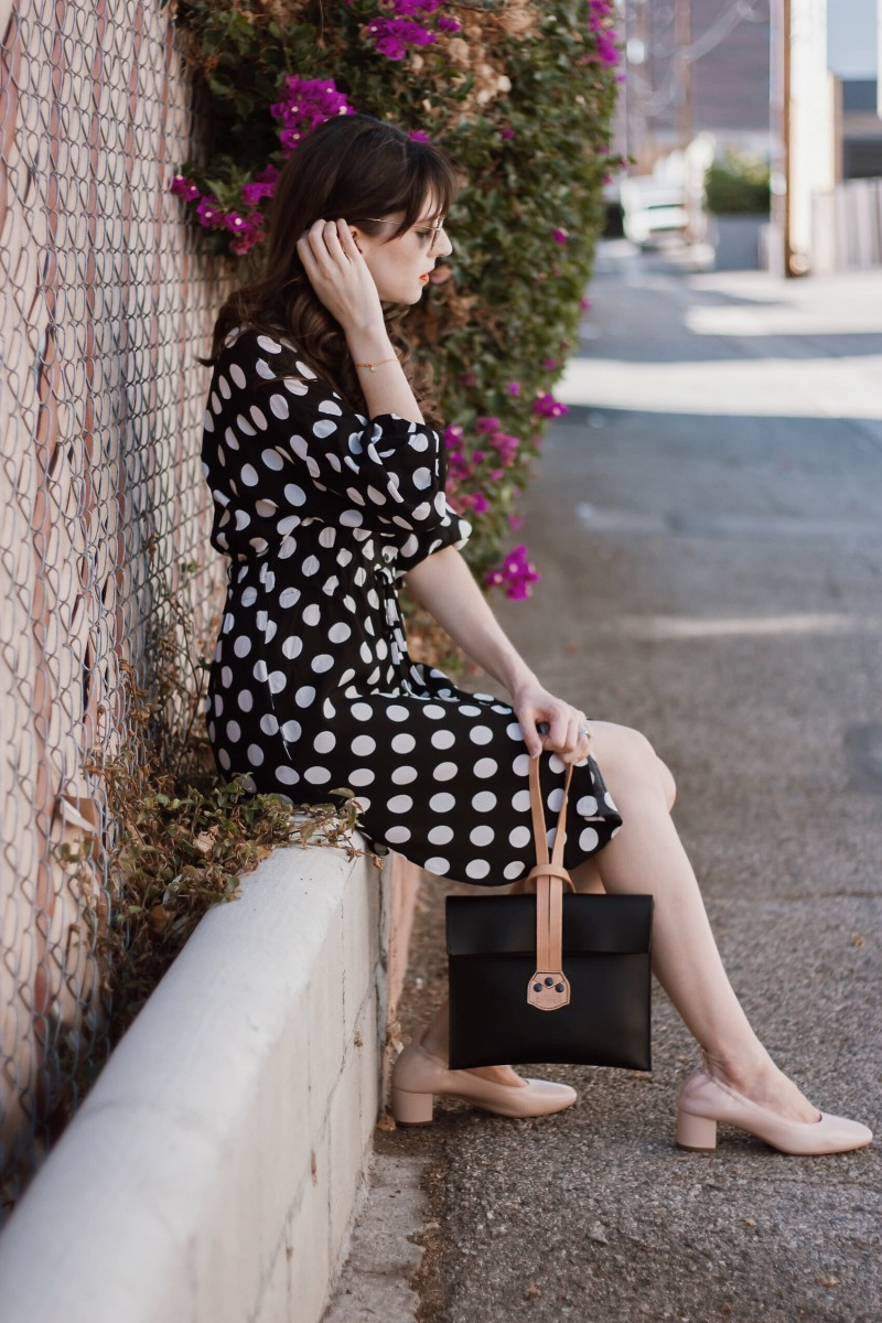 Los Angeles Fashion Blogger wearing a polka dot dress and minimalist clutch