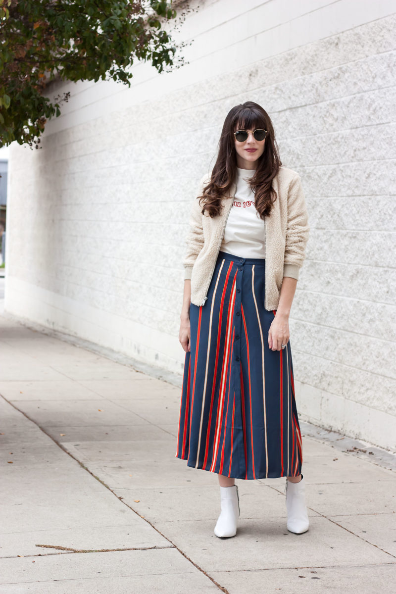 Fashion blogger wearing striped midi skirt, white booties, sherpa jacket and retro tee