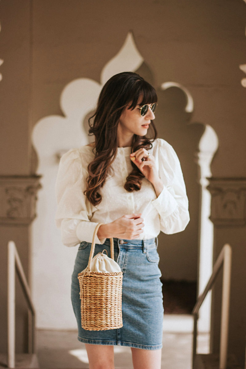 Minimalist Style Blogger wearing H&M Puff Sleeve Blouse, & Other Stories Denim Skirt, and Lulu's Straw Basket Bag