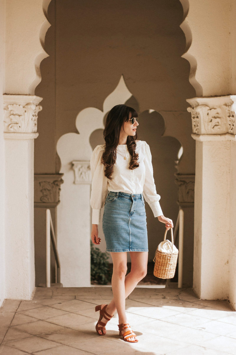 Los Angeles Blogger at the Brand Library wearing a straw basket bag, croc embossed sandals, puff sleeved top and denim skirt