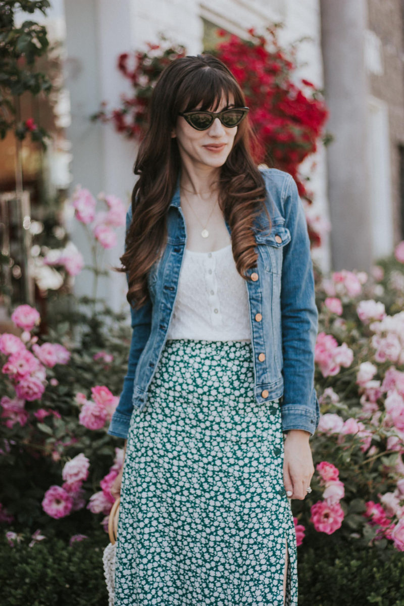 Feminine summer outfit featuring a floral midi skirt and denim jacket with slim cat eye sunglasses
