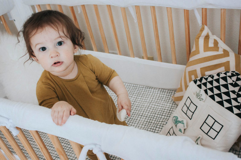 Baby boy in crib with Imani Collective pillow