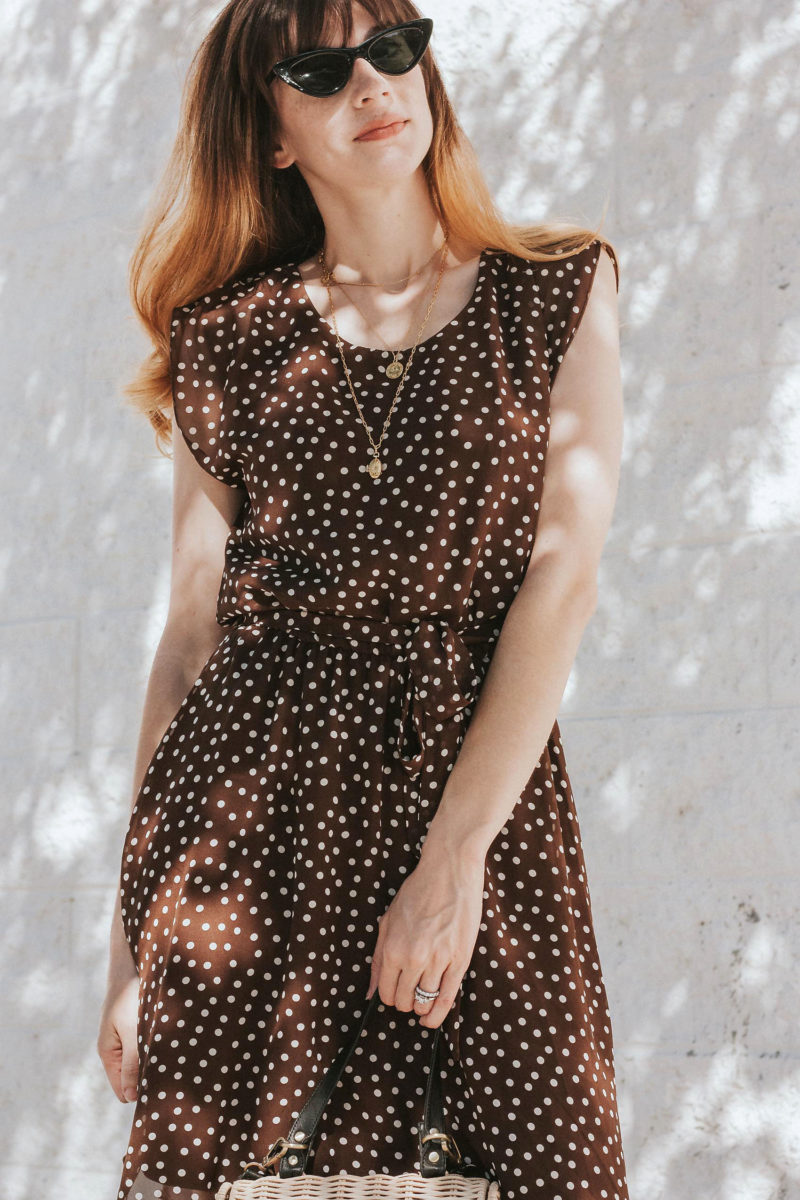 Los Angeles Minimalist fashion blogger wearing tie waist polka dot dress and layered gold jewelry.