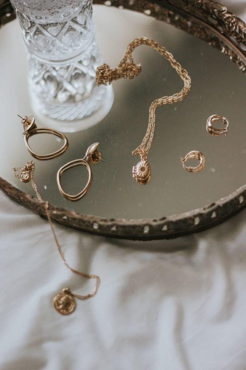 Minimalist Jewelry on vintage tray with Mejuri Locket Pendant, SOKO Earrings