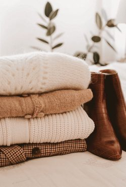 Sweaters in a stack with boots, how to store sweaters
