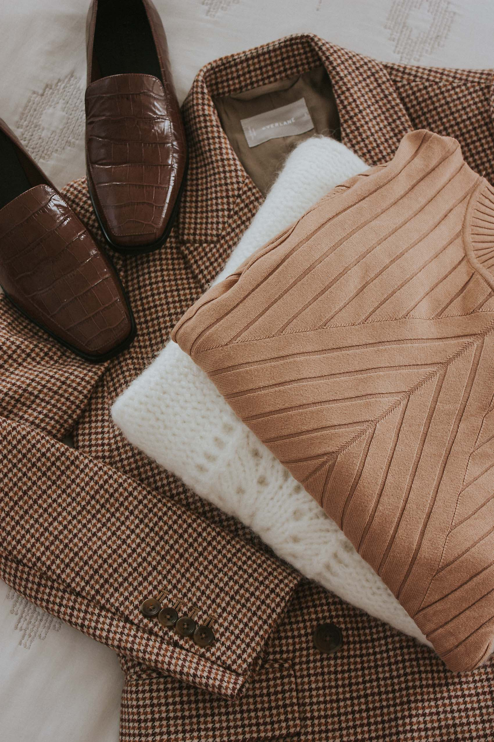 How to get your sweaters to last longer, stack of sweaters with blazer and shoes.