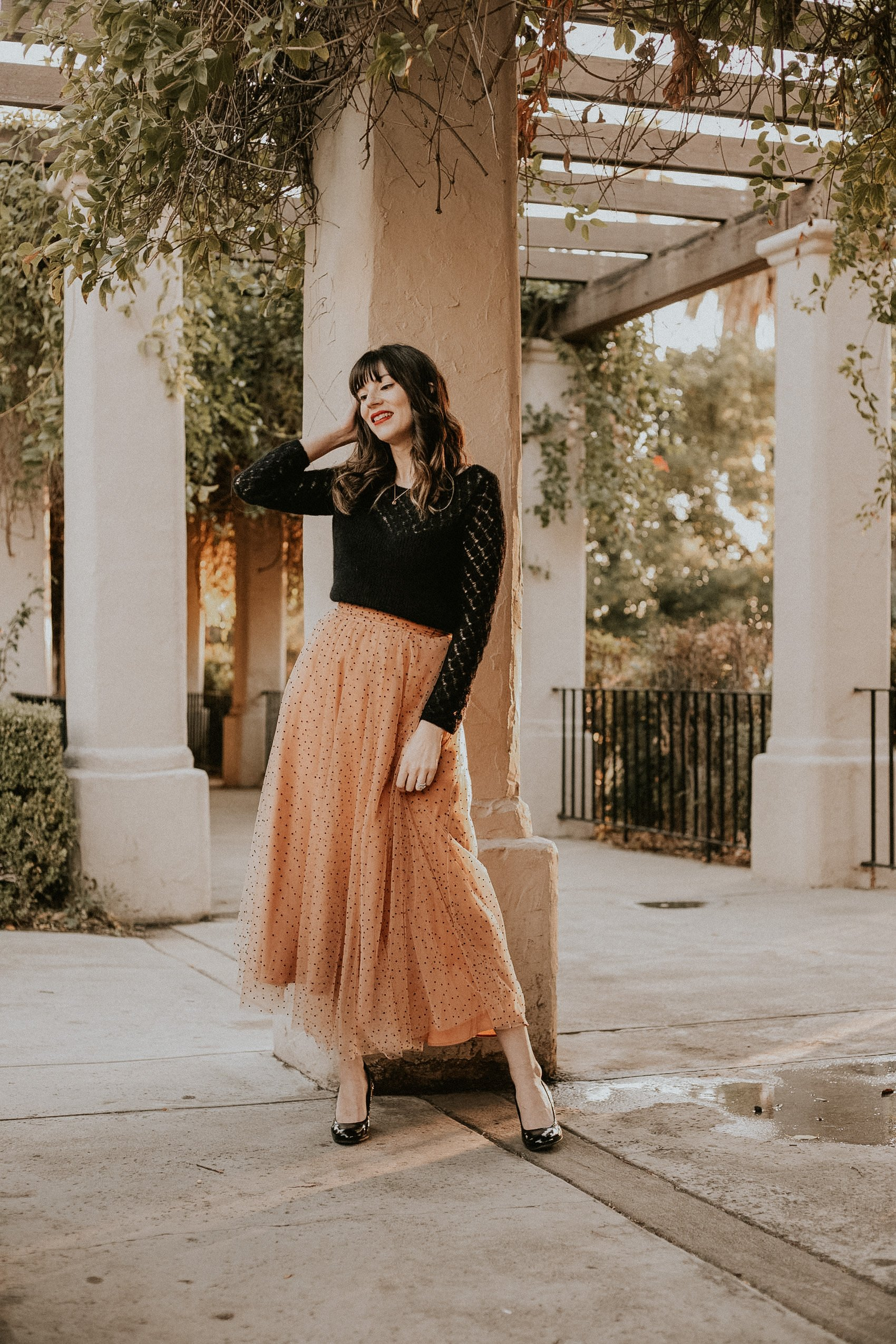 Fashion Blogger wearing a Christmas holiday outfit, champagne tulle skirt with black dots, black sweater and patent leather pumps