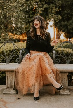 Fashion blogger on park bench wearing French Inspired holiday outfit, tulle skirt, black sweater, red lips