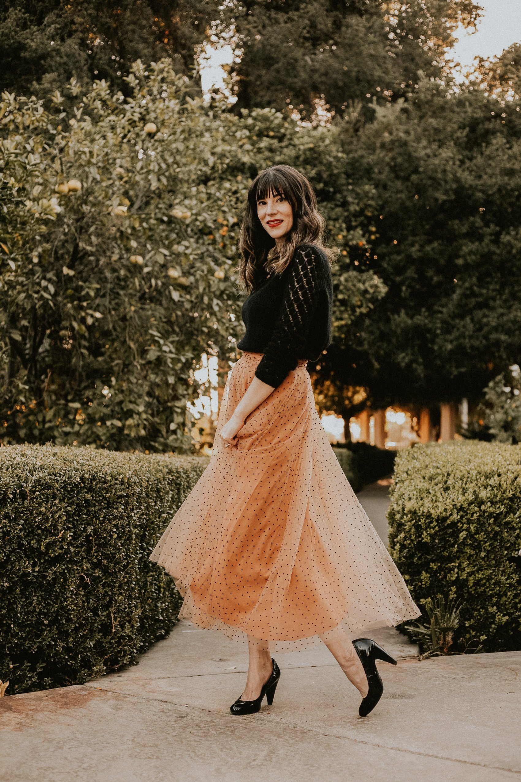 Los Angeles Fashion blogger in a park wearing an ankle length tulle skirt, black sweater, and pumps