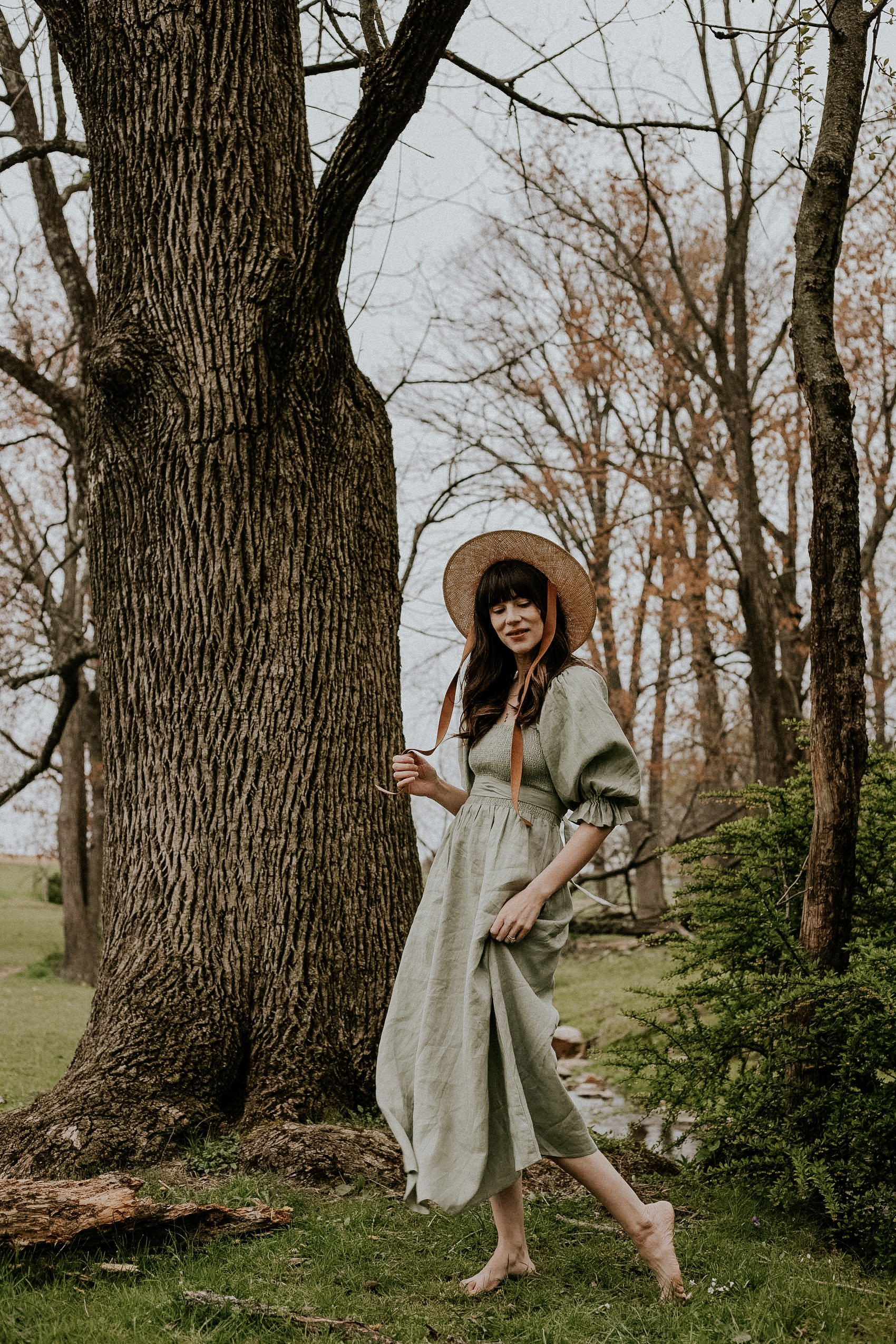 Aulieude Smocked Linen Dress with puff sleeve and straw hat on woman in the woods