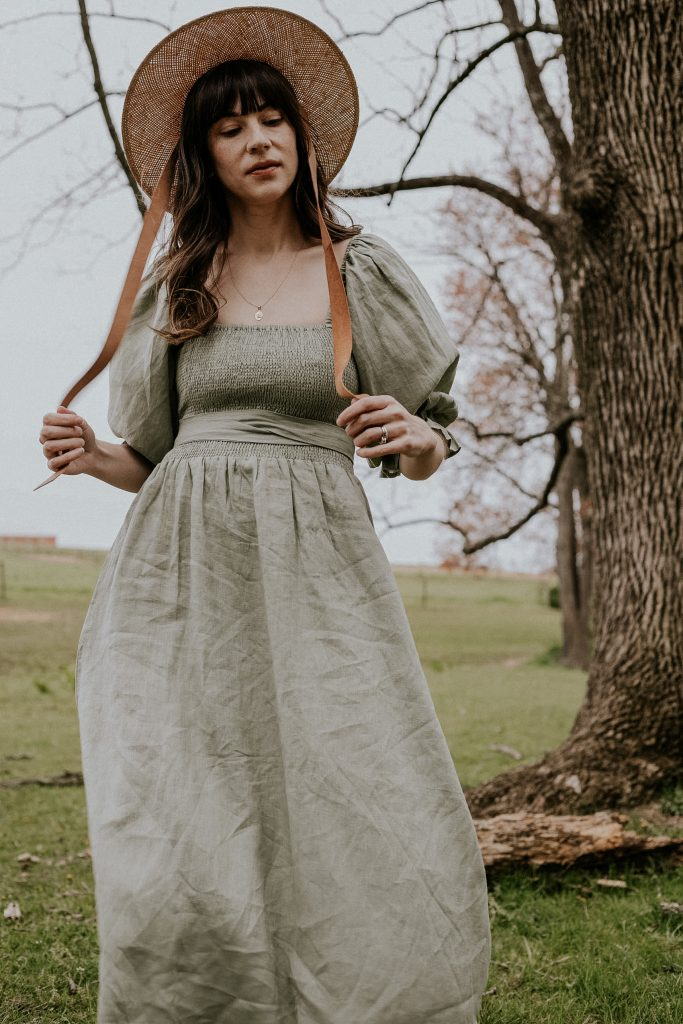 Smocked cottagecore dress with puff sleeves on woman wearing a straw hat with ties in field