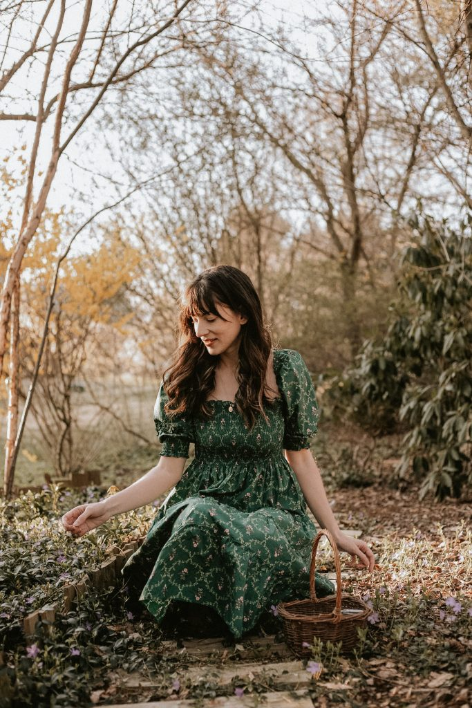 Green Puff Sleeve Cottagecore dress from Hill House on woman sitting in woods with flowers