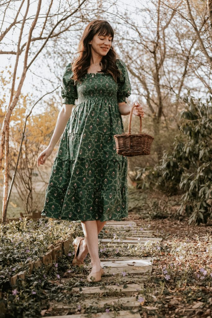 Hill House Nap Dress Review featuring The Nesli dress in Emerald on woman in the woods with basket