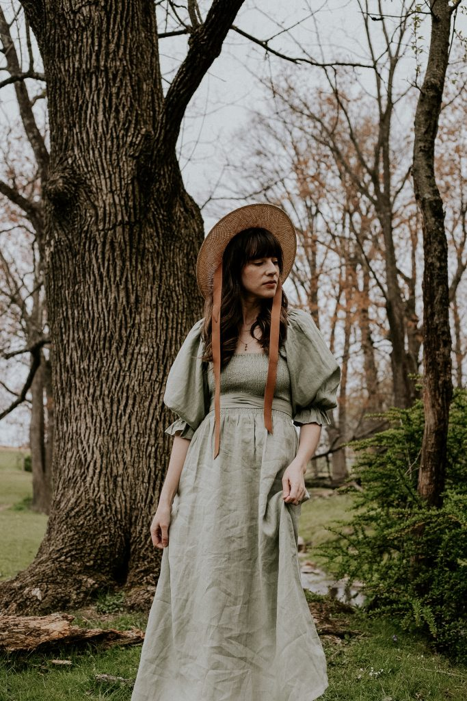 Sage Green linen dress with puff sleeves and straw hat on lancaster county blogger in woods