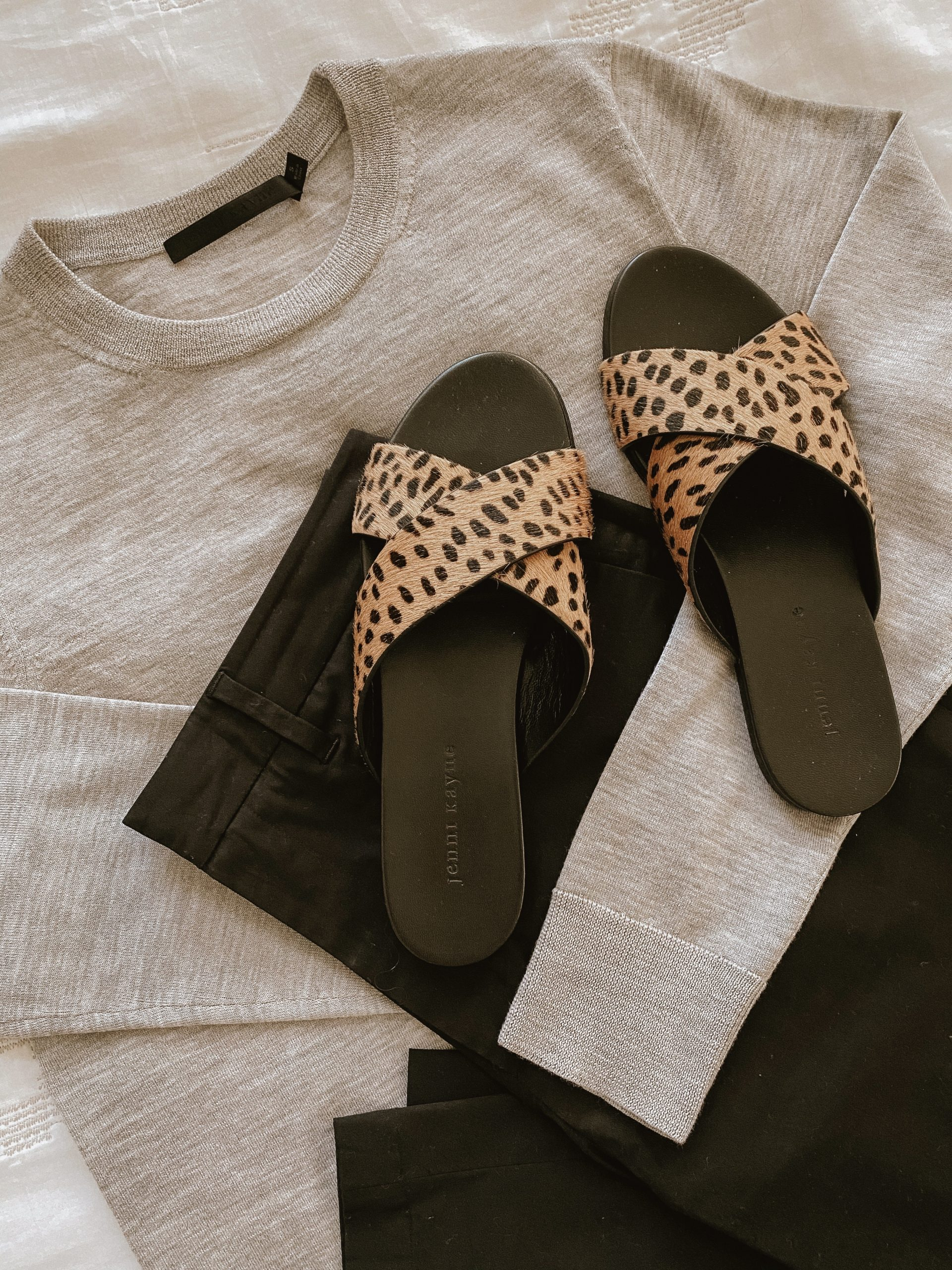 A review of the California Lifestyle Brand Jenni Kayne. Flatlay with Crosby Sweater, Twill Pants, Crossover sandals