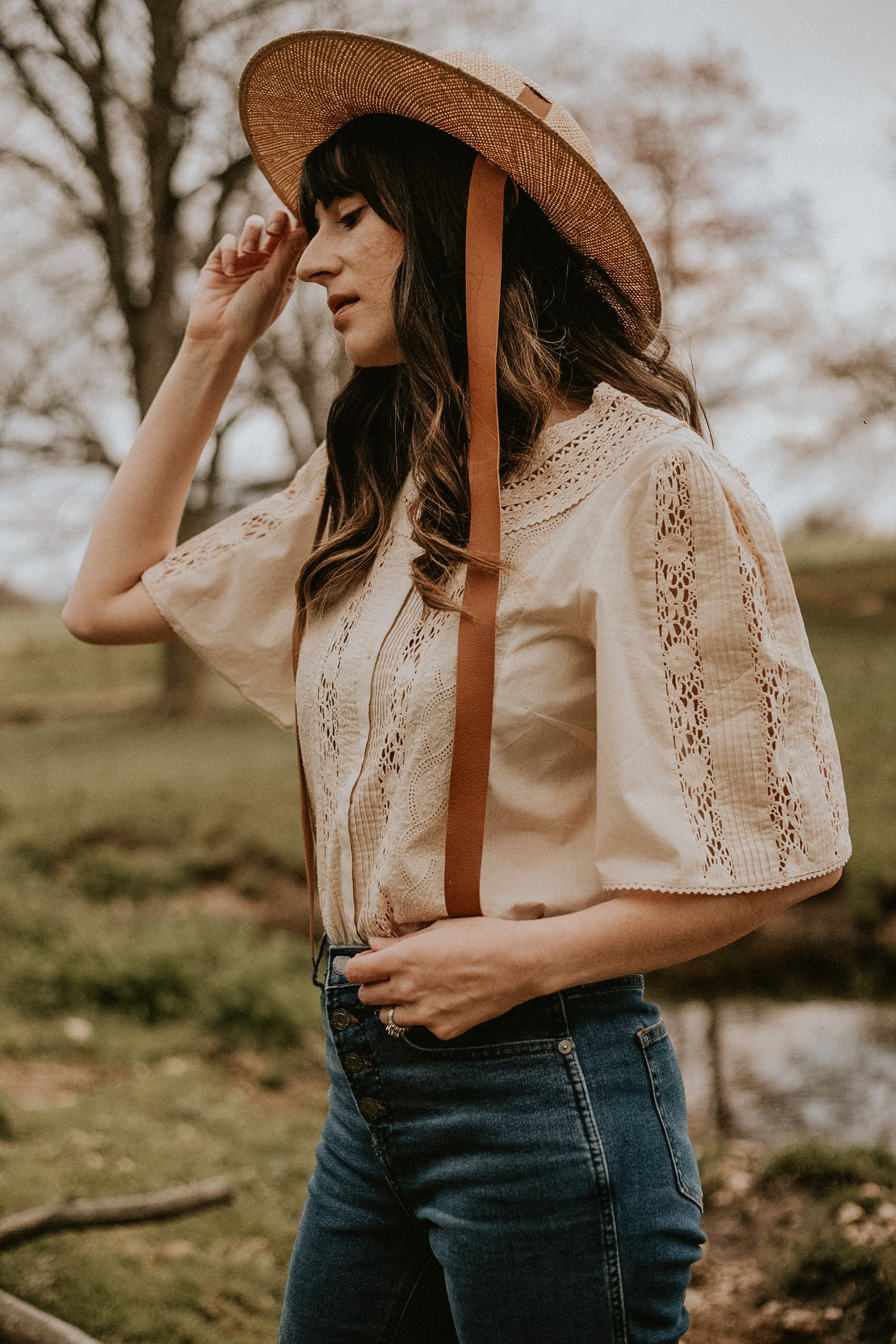 Sezane Embroidered Jane Blouse with Janessa Leone Straw Agnes hat with leather ties on woman in field
