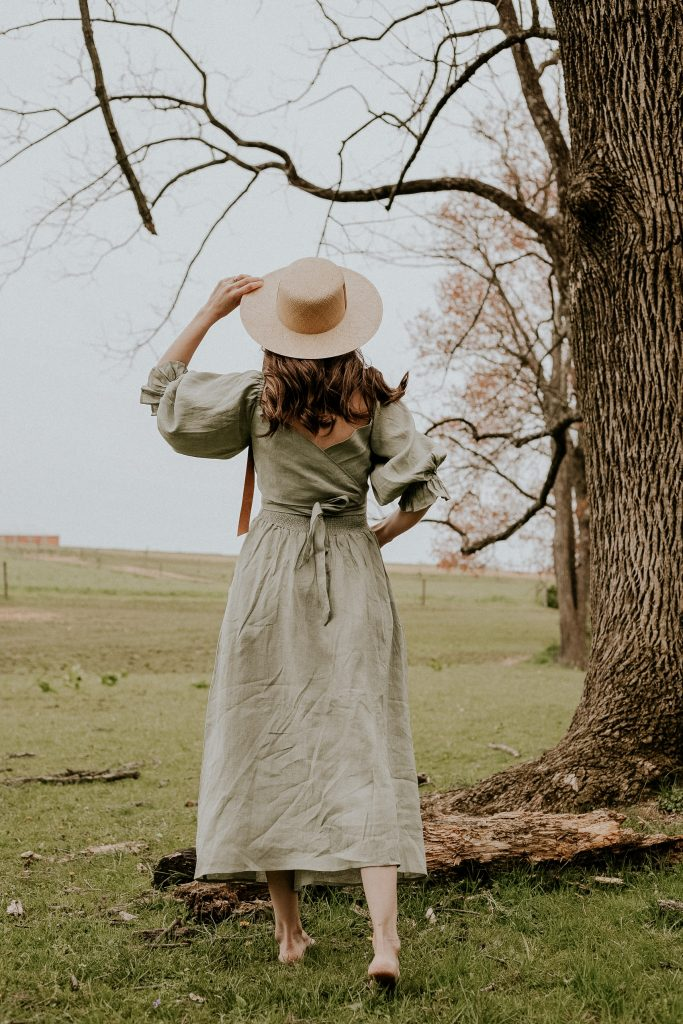 Reversible smocked dress from Aulieude and Janessa Leone straw hat on blogger in field