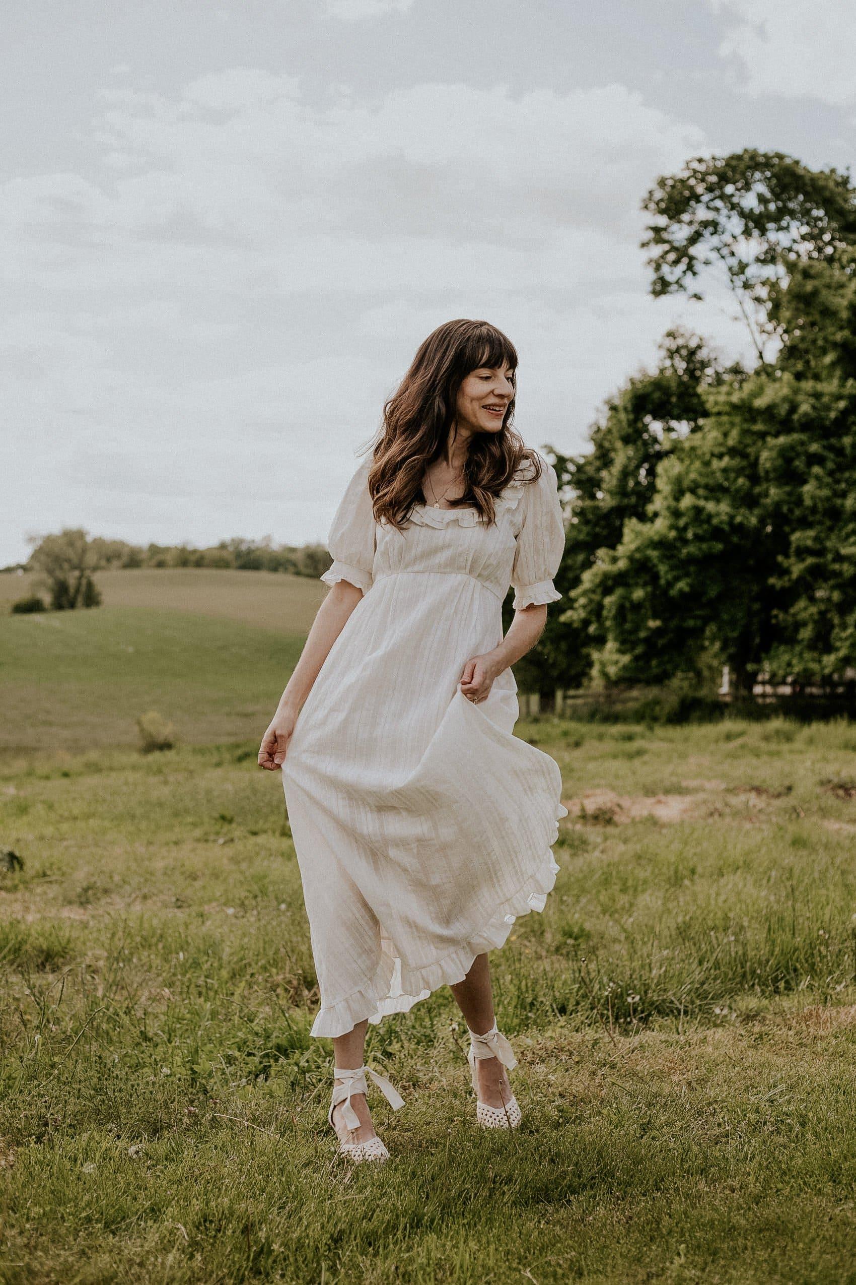 Bridgerton style white dress from Christy Dawn with Sezane espadrilles on woman in field