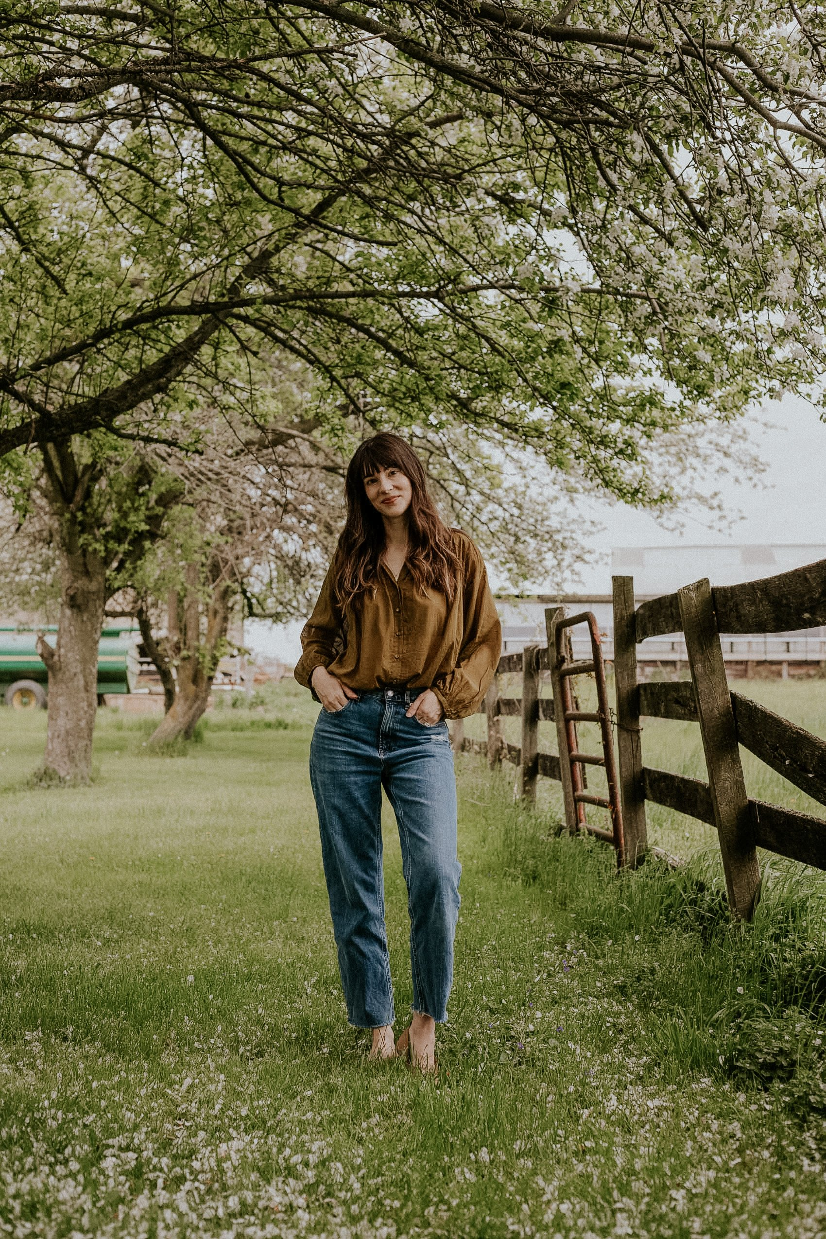 60s inspired outfit featuring the jane blouse from Doen and The Way High jeans from Everlane on woman in field