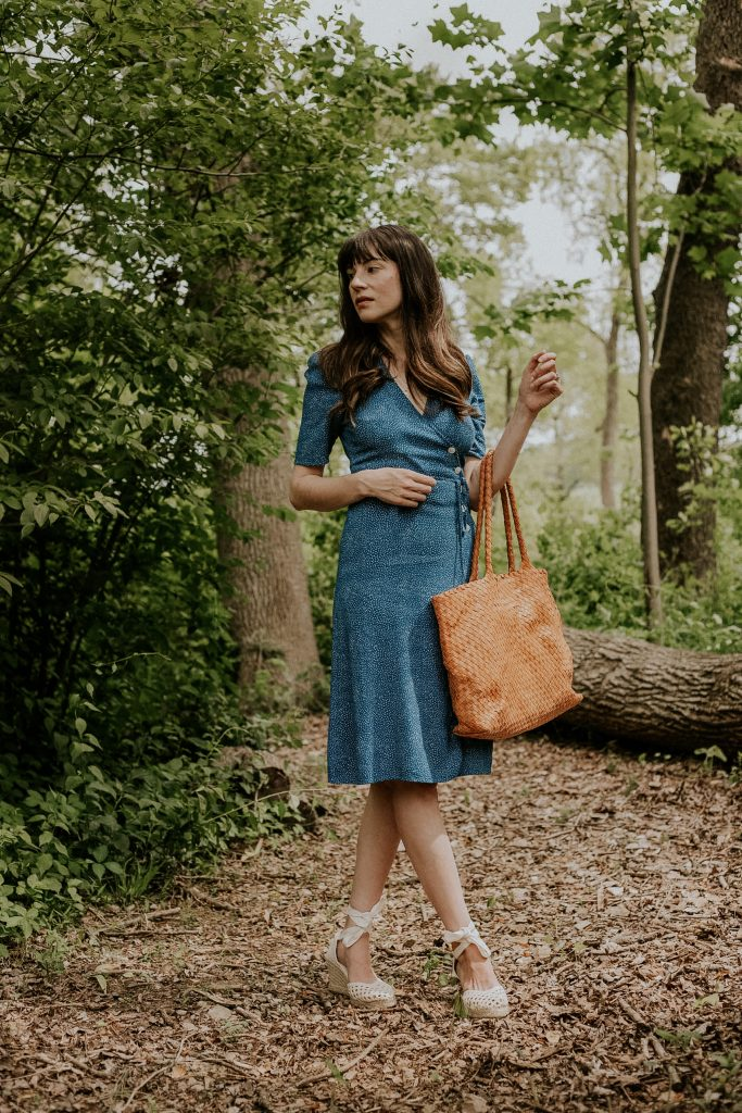 Blue Wrap Dress from Rouje with espadrille sandals and woven leather bag on woman in woods