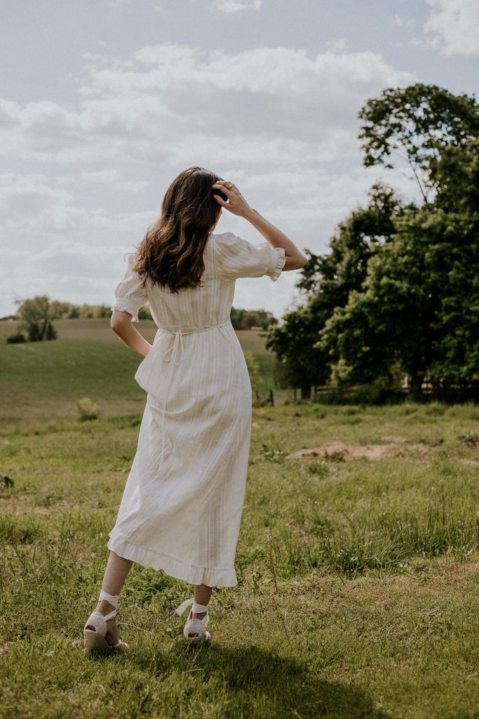 White summer dress from Christy Dawn with espadrilles on woman in field