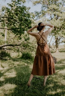 Everlane backless Pinafore Dress with adjustable straps on woman standing in a field