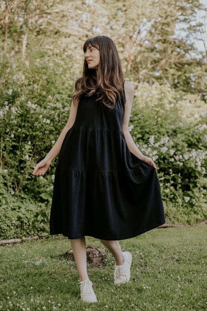 Everlane Sleeveless Weekend Tiered Dress in Black on woman wearing white sneakers