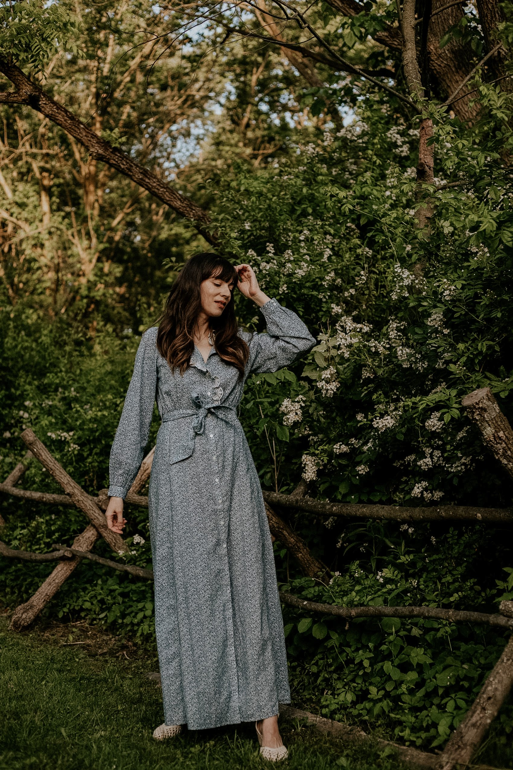 Sezane Long Blue Floral Dress with Tie Waist on Style Blogger standing in the woods