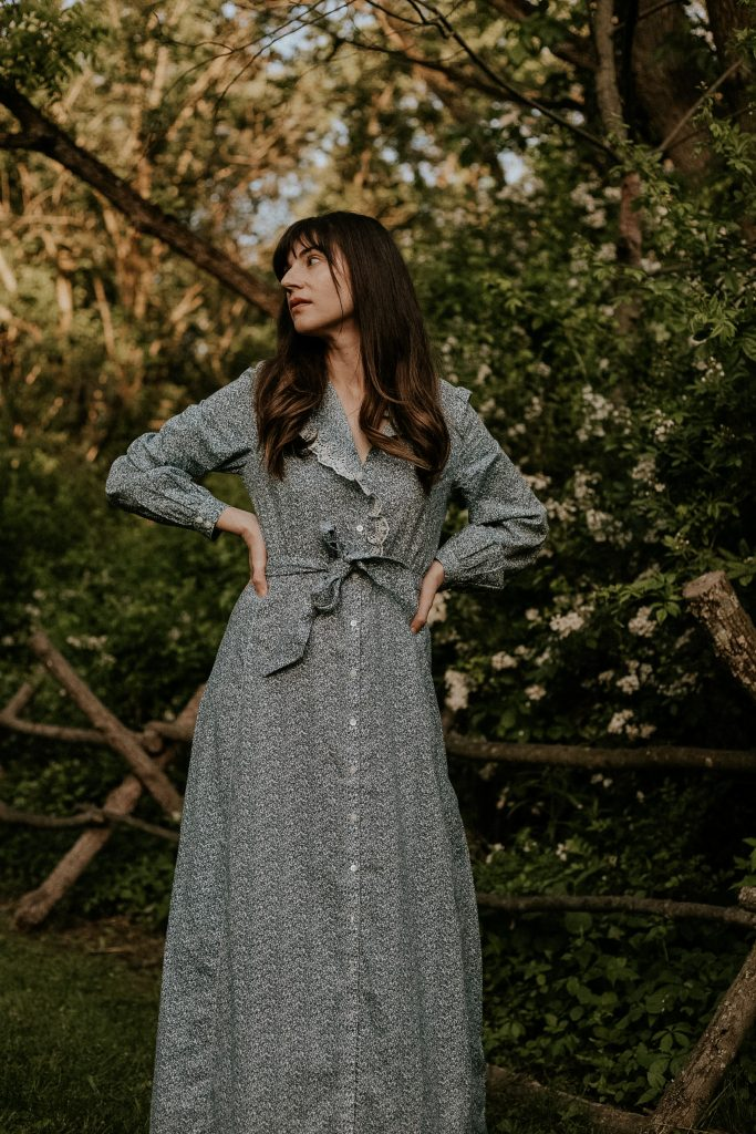 Blue Floral Prairie Dress on fashion blogger in the woods