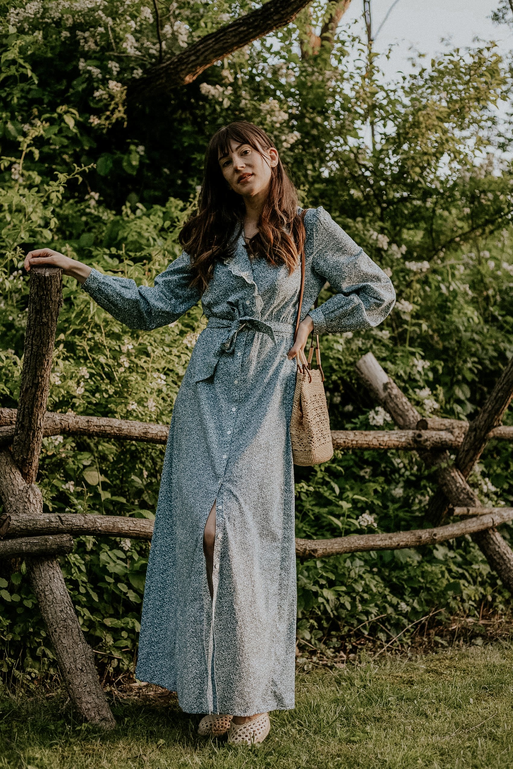 Blue Floral Prairie Dress and Woven Summer Bag on woman by fence