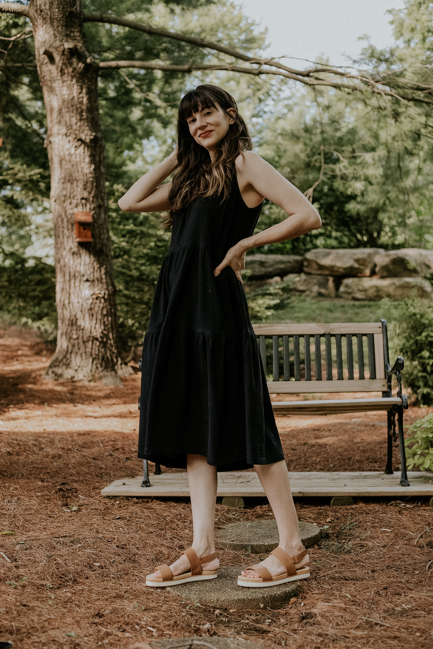 Nisolo go-to flatform sandals with Everlane black tank dress on woman standing near bench
