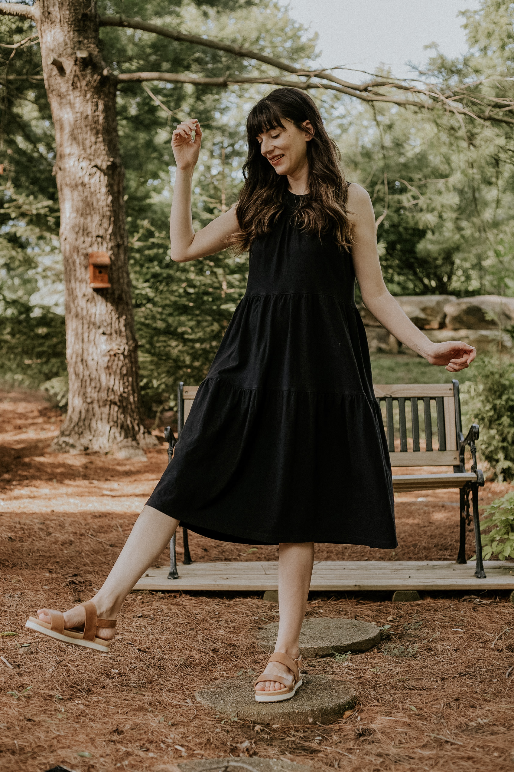 Woman standing near bench wearing Everlane tiered tent dress with Nisolo Flatform Sandals