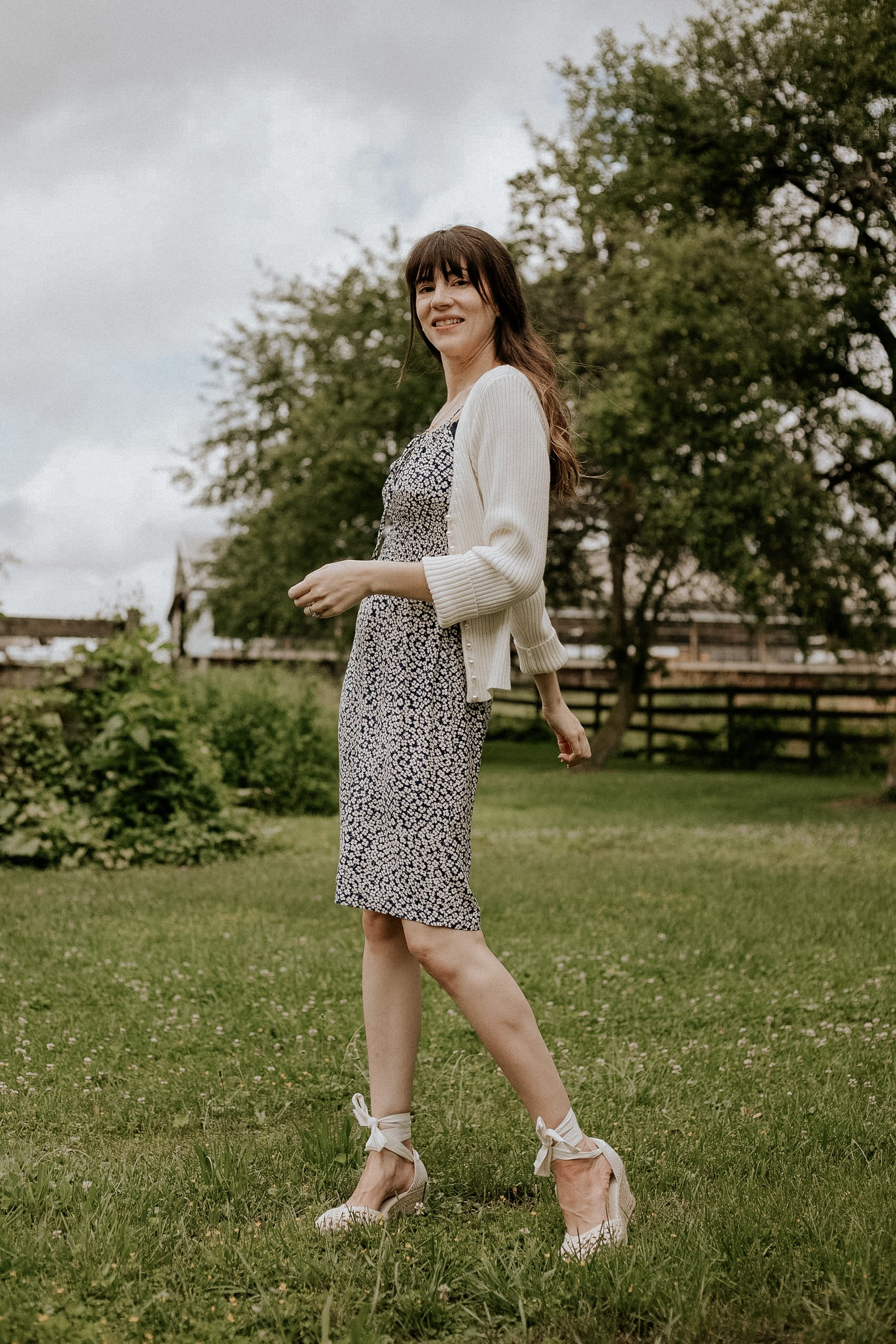 A french girl summer outfit on woman in farm field wearing rouje dress and espadrilles