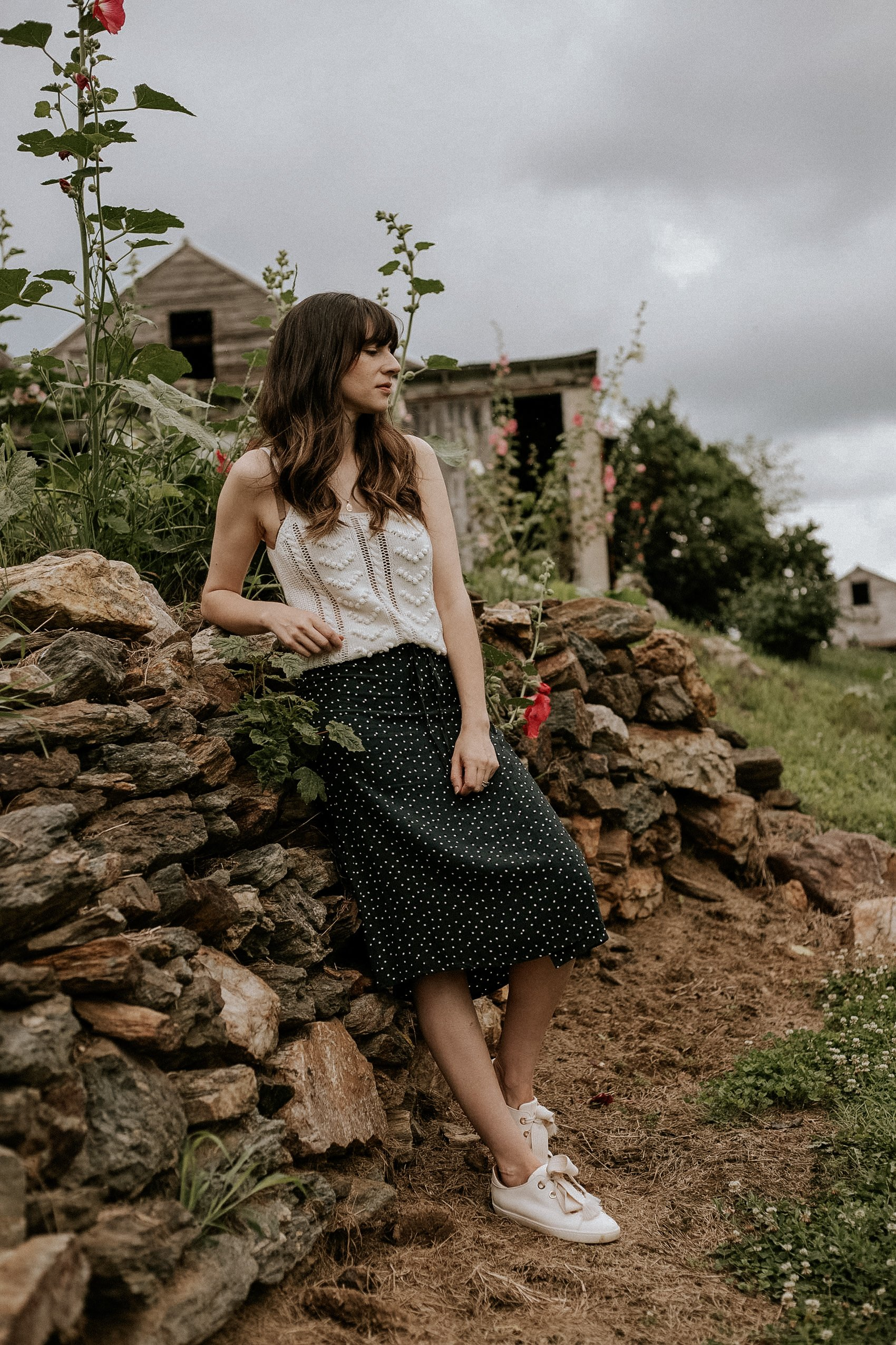 Sézane Jack Sneakers with polka dot midi skirt and textured knit tank on woman leaning on a stone wall