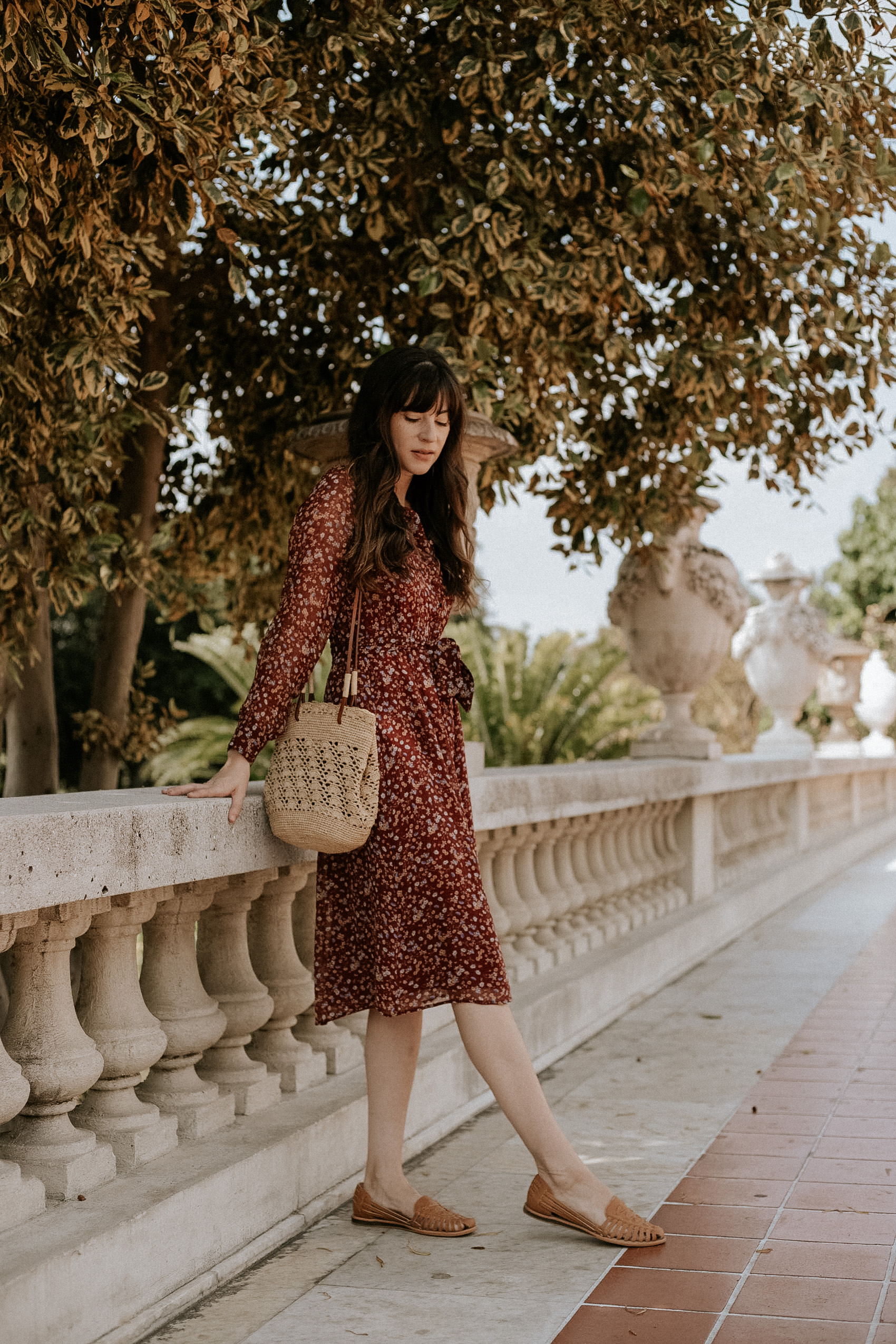 Nisolo Huarache Sandals with Sezane Alix Dress on woman standing against wall