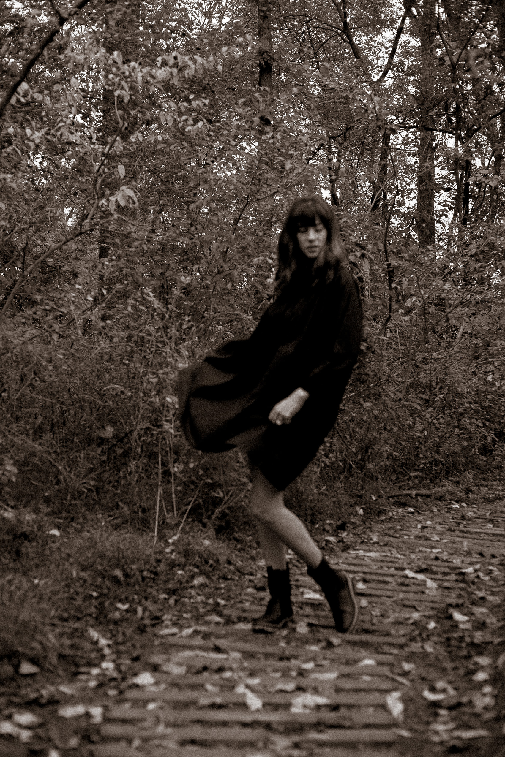 All black fall outfit on woman in woods giving off spooky vibe